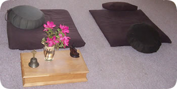 Photo of dokusan room with bell and flowers in vase.