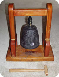 Photo of Zen Buddhist bronze bell in wood frame with wooden hammer.